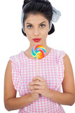 Serious black hair model holding a colored lollipop Stock Images