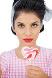 Serious black hair model holding a heart shaped lollipop Royalty Free Stock Photos