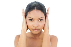 Serious black haired model blocking her ears Stock Image