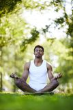 Serious black man with crossed legs meditating in park. Serious concentrated young black man with crossed legs keeping eyes closed and holding hands in mudra stock images