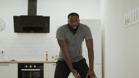 Serious black man dancing hip hop at kitchen. Young dancer warming up at home. stock footage