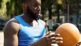 Serious black man sitting alone at stadium and throwing ball, preparing for game. Stock photo stock photography