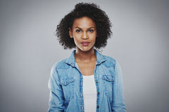 Serious black woman with blue jean shirt. Serious beautiful black woman with blue jean shirt on gray background Stock Image