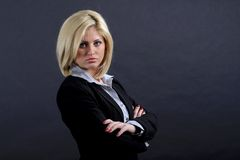 Serious blond businesswoman. Half body portrait of serious blond businesswoman with arms folded; studio background Stock Images