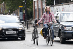 Serious blond curly bearded man in a plaid shirt riding a bike and holding a second bike for the wheel in Shoreditch. Royalty Free Stock Images