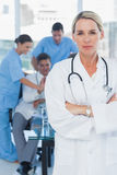 Serious blond doctor posing with colleagues in background Stock Photography