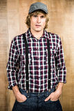 Serious blond hipster staring at camera. With wooden background Royalty Free Stock Photos