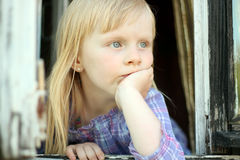 Serious blond little girl looking out the window Royalty Free Stock Image