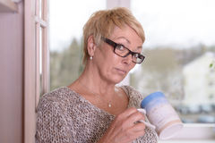 Serious Blond Woman with Glasses Holding a Cup Royalty Free Stock Images