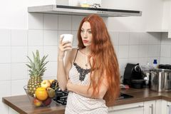 Serious Blond Woman Holding A Glass at the Kitchen Stock Photography