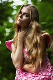 Serious blond woman in pink dress. In forest Royalty Free Stock Images