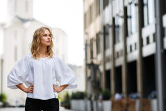 Serious blond woman standing outdoors and looking thoughtfully into distance Royalty Free Stock Photos