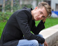 Serious blond young man in jeans and jacket, sitting outdoors. Serious or sad blond young man in jeans and jacket, sitting outdoors looking in camera Royalty Free Stock Photos