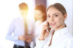 Serious blonde businesswoman talking by phone in the background of her colleagues in office. Business concept stock photography
