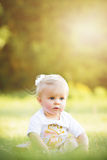 Serious blonde haired toddler girl sitting outside stock photos