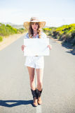 Serious blonde holding sign while hitchhiking on the road. In summertime Stock Images