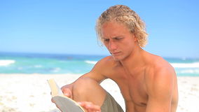 Serious blonde man reading a novel. On the beach stock video footage