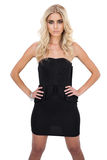 Serious blonde model in black dress posing hands on the hips Royalty Free Stock Images