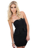 Serious blonde model in black dress posing looking at camera. On white background Royalty Free Stock Photos