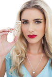 Serious blonde model in blue dress holding a eyelash curler Royalty Free Stock Images