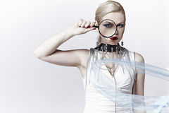 Serious blonde in a retro style with a magnifier Stock Images