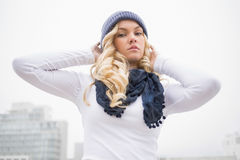 Serious blonde in winter clothes posing outdoors Stock Photography
