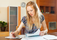 Serious blonde woman fills in documents Stock Images