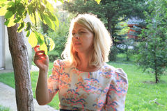 Serious blonde woman looking at leaves in the park Royalty Free Stock Image