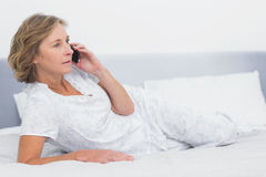 Serious blonde woman lying on bed making a phone call Stock Photography
