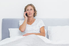 Serious blonde woman making phone call in bed Royalty Free Stock Photography