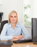 Serious blonde woman sitting behind a desk. In an office Stock Photo