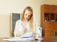 Serious blonde woman staring financial documents Stock Image