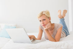 Serious blonde woman using laptop Stock Images