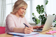 Serious blonde writing while working in laptop Royalty Free Stock Image