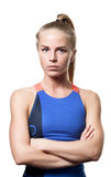 Serious Blue eyed blond girl. With tail hair in sportswear with crossed arms and front standing on white isolated background Royalty Free Stock Photo