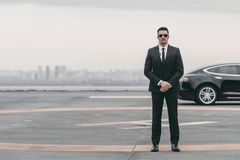 serious bodyguard standing with sunglasses and security earpiece on helipad and looking stock images