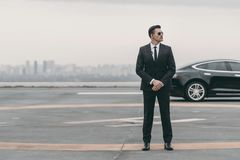 serious bodyguard standing with sunglasses and security earpiece on helipad and looking royalty free stock photos