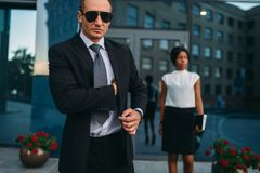 Serious bodyguard in suit, sunglasses and earpiece stock photo