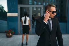 Serious bodyguard in suit and sunglasses, guarding stock image