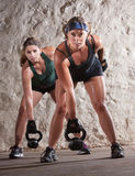 Serious Boot Camp Style Workout. Serious pair of young women lifting weights during boot camp workout Royalty Free Stock Photography