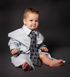 Serious boss baby wearing over sized suit Royalty Free Stock Image