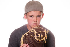 Serious Boy with baseball and glove. Boy frowning while holding a baseball and glove stock image