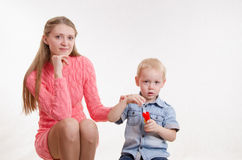 Serious boy blow bubbles with her mother Royalty Free Stock Images