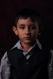 Serious boy on brown background Royalty Free Stock Photos