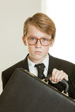 Serious boy in business suit and brief case stock image