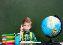 Serious boy in classroom showing finger up.  Stock Images