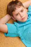 Serious boy on the floor Royalty Free Stock Images