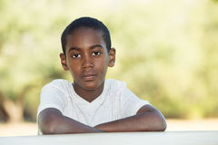 Serious boy with folded arms at table Royalty Free Stock Images