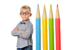 Serious boy in glasses and bowtie posing near huge colorful pencils. Educational concept. Isolated over white. Royalty Free Stock Photos