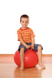Serious boy with gymnastic ball. Serious little boy sitting on a gymnastic rubber ball - isolated Royalty Free Stock Images